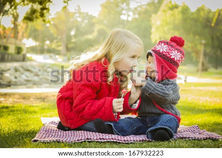 Little Girl with Her Baby Brother Wearing Winter Coats and Hats Sharing a Lollipop Outdoors at the Park.  - stock photo