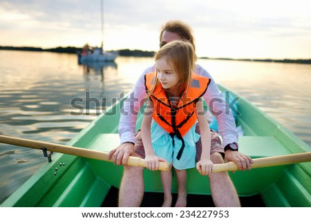 Little girl with her father on a boat on warm and beautiful summer day - stock photo