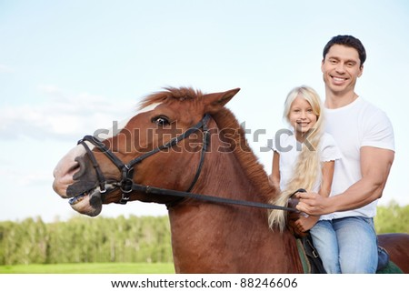 Little girl with her father on a horse - stock photo