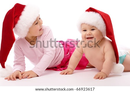 Little girl with her little brother, both wearing red Christmas caps and smile, isolated over white - stock photo
