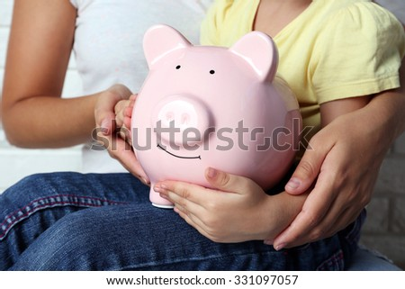 Little girl with her mum and pig  moneybox closeup - stock photo