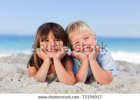 Little girl with his brother on the sand - stock photo