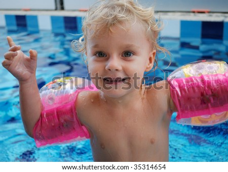 Little girl with inflatable over-sleeves floats in pool - stock photo