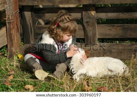 little girl with lamb on the farm - stock photo