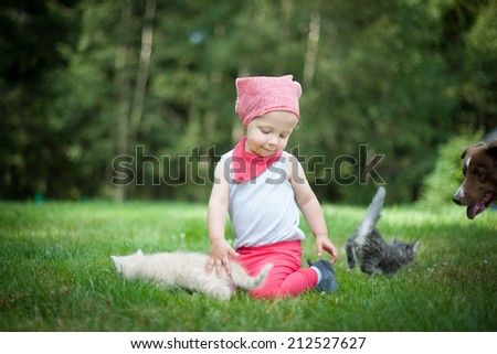 Little girl with large dog and cats - stock photo