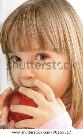 little girl with large gray eyes bite the apple - stock photo
