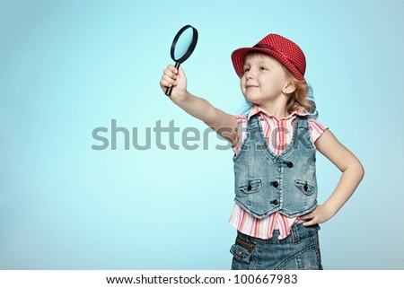 Little girl with magnifying glass, isolated on a blue background - stock photo