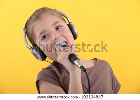 Little girl with microphone and headphones - stock photo