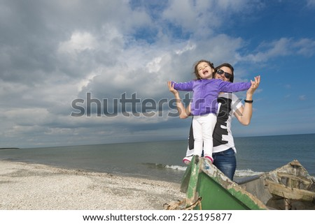 Little girl with mom having fun on the beach in a old boat against blue cloudy sky - stock photo