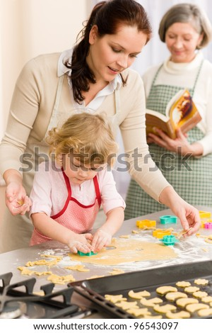Little girl with mother cutting out cookies in kitchen - stock photo