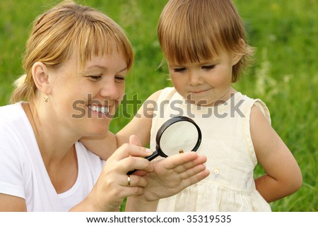Little girl with mother looking at little snail through magnifying glass - stock photo