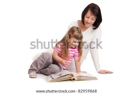 Little girl with mother looks family album isolated - stock photo