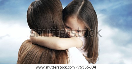 Little girl with nice hair hugs his mother - stock photo
