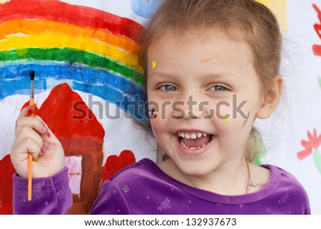 little girl with paint brush and painting - stock photo