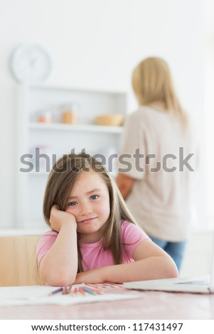 Little girl with paper and colouring pencils leaning on kitchen table with mother standing behind - stock photo