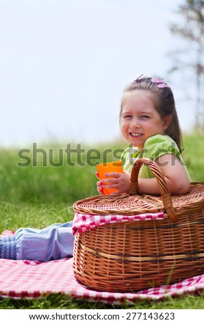 Little girl with picnic basket and plastic cup at lawn - stock photo