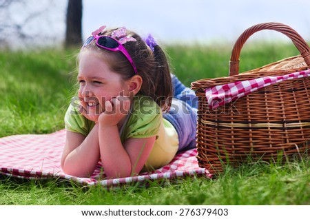 Little girl with picnic basket at lawn - stock photo