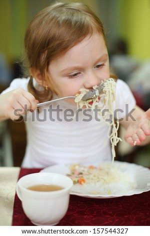 Little girl with pigtails eating spaghetti with a spoon in a cafe - stock photo