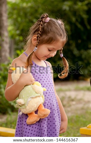 Little girl with pigtails nursing a toy. - stock photo