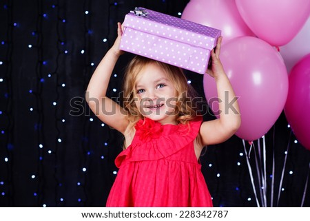 Little girl with pink balloons and gift boxes - stock photo