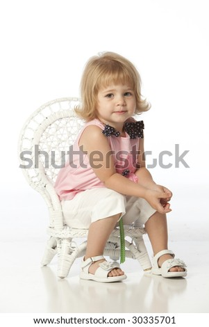 Little girl with pink flower dress seated in wicker chair - stock photo