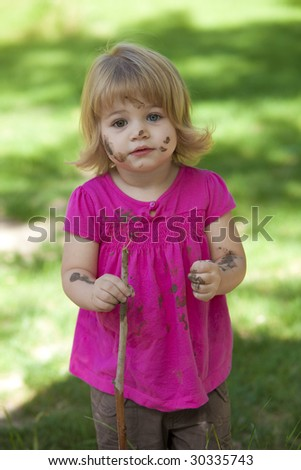 Little girl with pink shirt and muddy face - stock photo