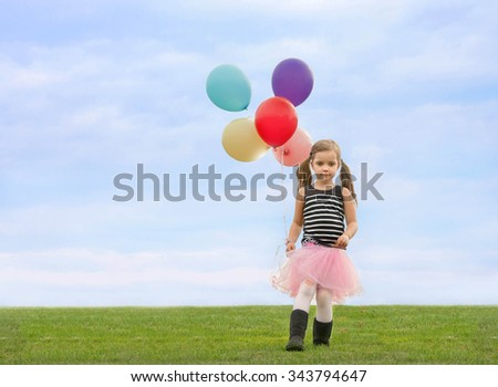 little girl with pony tails walking down the lawn with a bunch of helium filled high float colorful baloons in her hand - stock photo