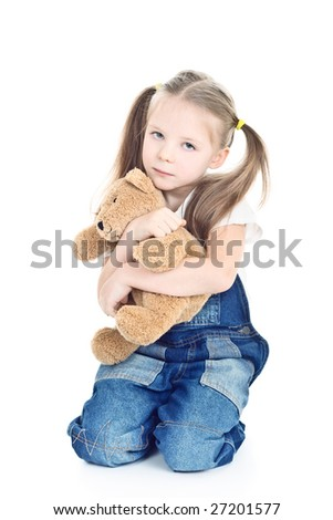 little girl with ponytails hugging her toy bear - stock photo