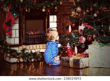 little girl with presents at christmas home - stock photo