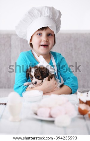 Little girl with puppy prepare dessert zephyr - stock photo