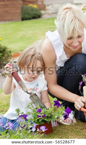 Little girl with purple flowers and garden tool - stock photo