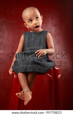 Little girl with shaved head shows the gesture of surprise in a red background - stock photo
