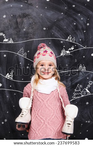 Little girl with skates on his neck standing near the mountains - stock photo