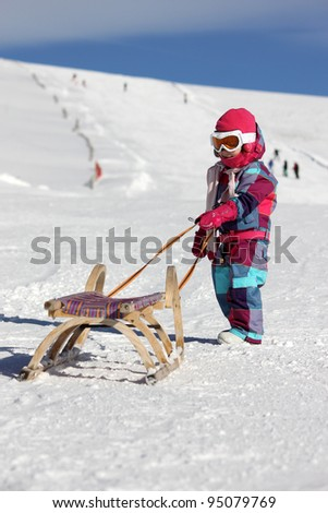 Little girl with sled - stock photo