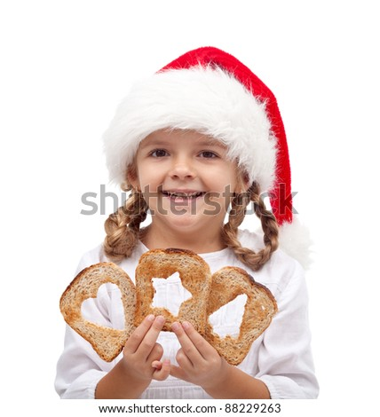 Little girl with slices of bread and santa hat - sharing and love at christmas time concept - stock photo
