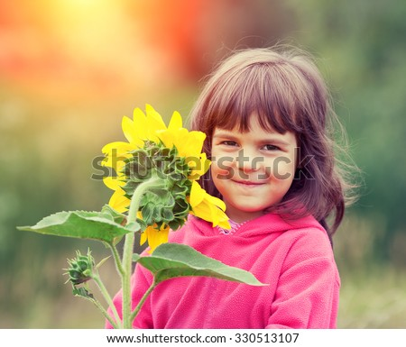 Little girl with sunflower outdoors - stock photo