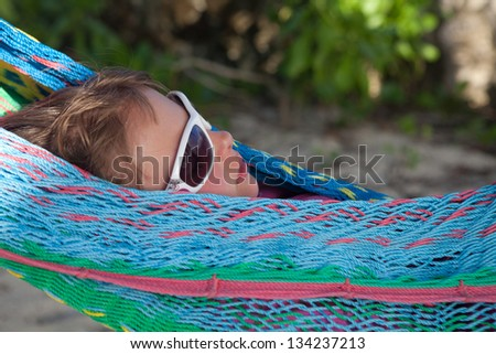 Little girl with sunglasses on a hammock - stock photo