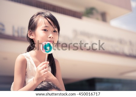 Little girl with sweet candy from low angle vintage style,dark tone - stock photo