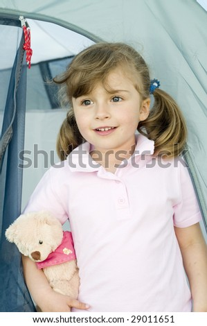 Little girl  with teddy bear in tent - stock photo
