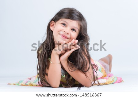 Little girl with tender gesture lying on the floor - stock photo