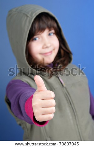 little girl with thumb up on blue background - stock photo