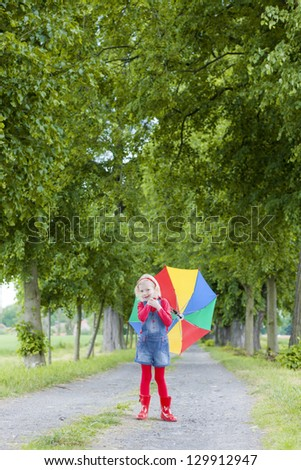 little girl with umbrella in alley - stock photo