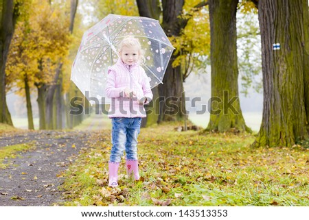 little girl with umbrella in autumnal alley - stock photo