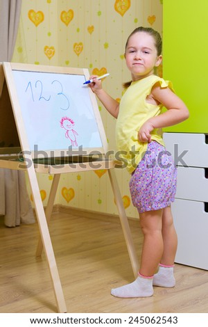 Little girl with whiteboard at home - stock photo