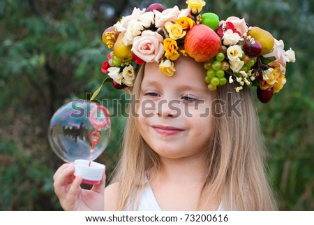 little girl with wreath from flowers blows soap bubbles - stock photo