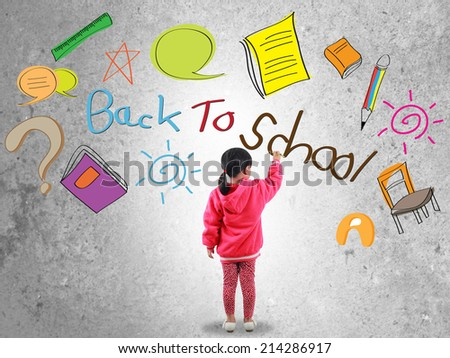 Little girl writing back to school text on wall  - stock photo