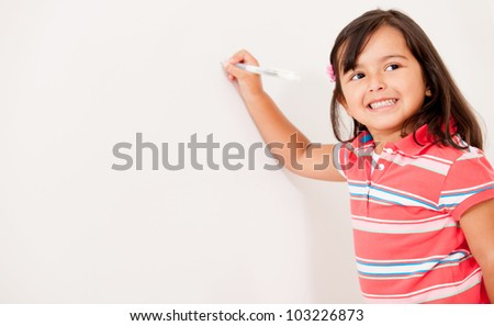 Little girl writing on the board and smiling - stock photo