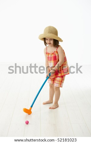 Little girl (4-5 years) in summer dress and straw playing golf indoor. White background. - stock photo