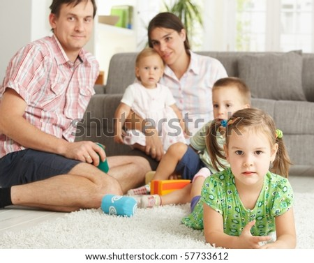 Little girl (3-4 years) lying on floor at home with nuclear family in background.? - stock photo