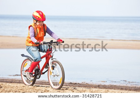 Little girlcycling along the beach - stock photo